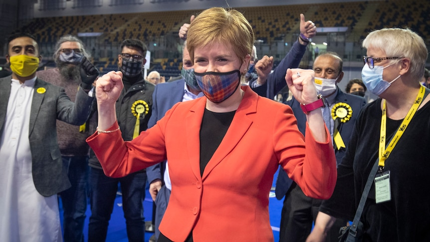 Wearing a red jacket and tartan facemask, Nicola Sturgeon clenches her fists in a victory gesture in front of supporters
