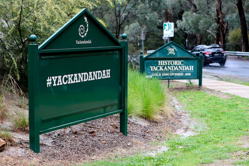 Two green signs welcoming motorists to Yackandandah with car passing on road