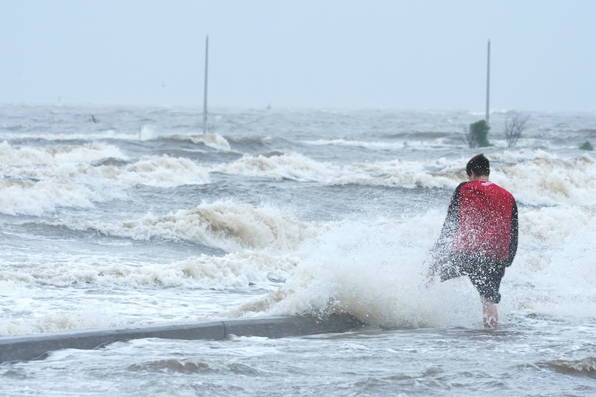 A person watches the wind and waves at the Gulfport Municipal Marina as outer bands of Hurricane Ida