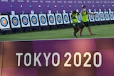 Two people walk in front of archery targets with the sign 'Tokyo 2020' in the foreground.