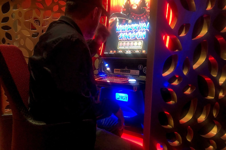 Man wearing black shirt and cap sits backed turned to camera at neon pokie machine.