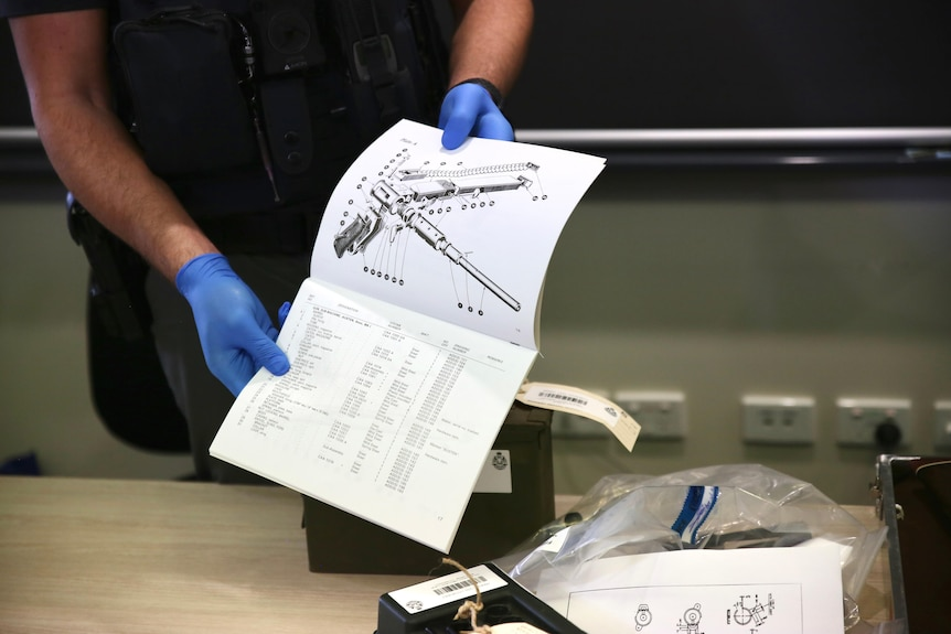 A police officer wears blue gloves while holding a booklet with a black and white diagram of gun components.