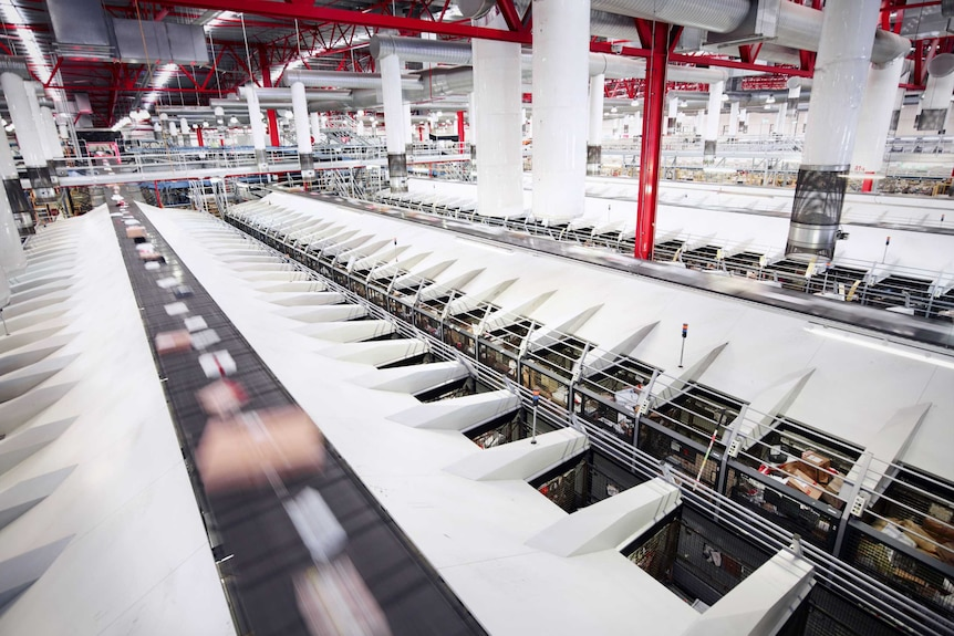 Parcels flying by on a conveyor belt inside a large red and white postal facility.