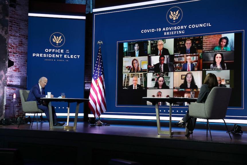 Joe Biden and Kamala Harris sit at desks as they receive a briefing via a video call.