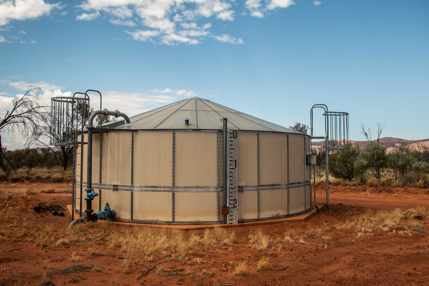 A large tank sits in front of a mountain range on red dirt. A water level meter is attached to the front of it.