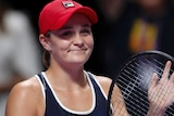 Ash Barty smiles and claps on her racquet while looking at the crowd.