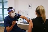 Male nurse vaccinating a woman