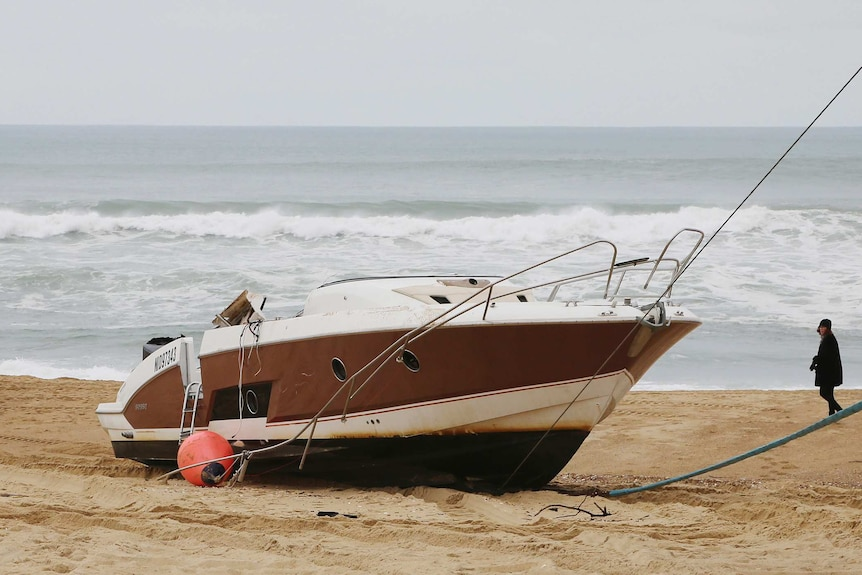 Image of a damaged speedboat washed ashore on a beach in France