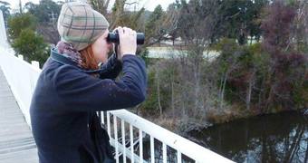 Woman with binoculars looking for platypus