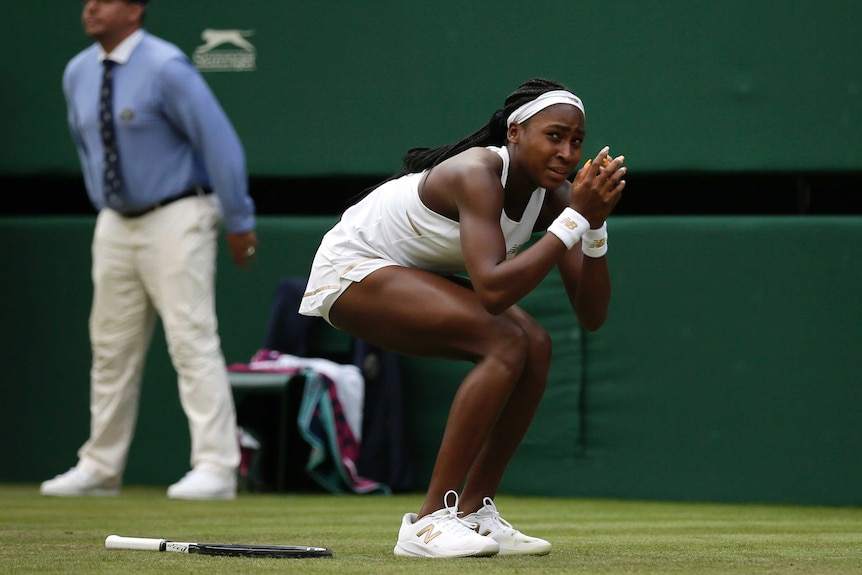 Coco Gauff bends down and hides her face in her hands with her racquet by her side