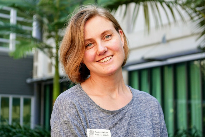 Blonde woman smiling at camera and wearing a grey shirt and hospital name tag that reads 'Mariann Hadland Caseload Midwife'.