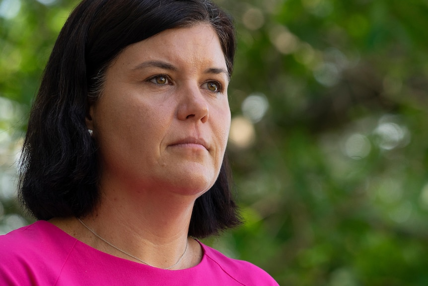 Natasha Fyles is wearing a pink shirt and looking serious into the distance.