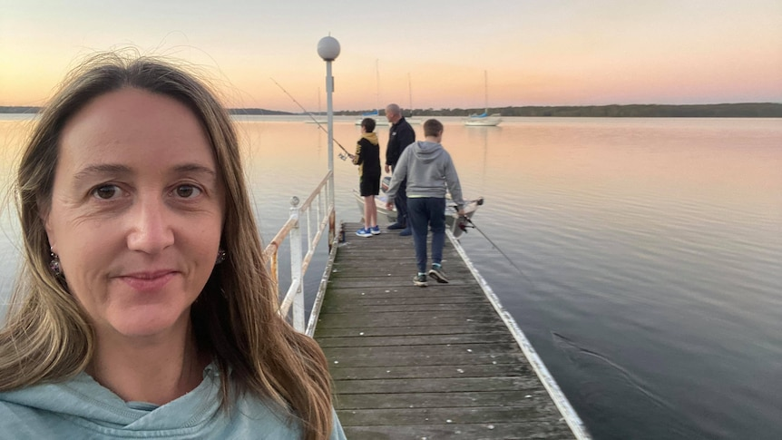 Amanda takes a selfie with her family in the background in a story about home and contents insurance.
