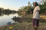 Naomi Wilfred stands by a river, as children sit on the banks