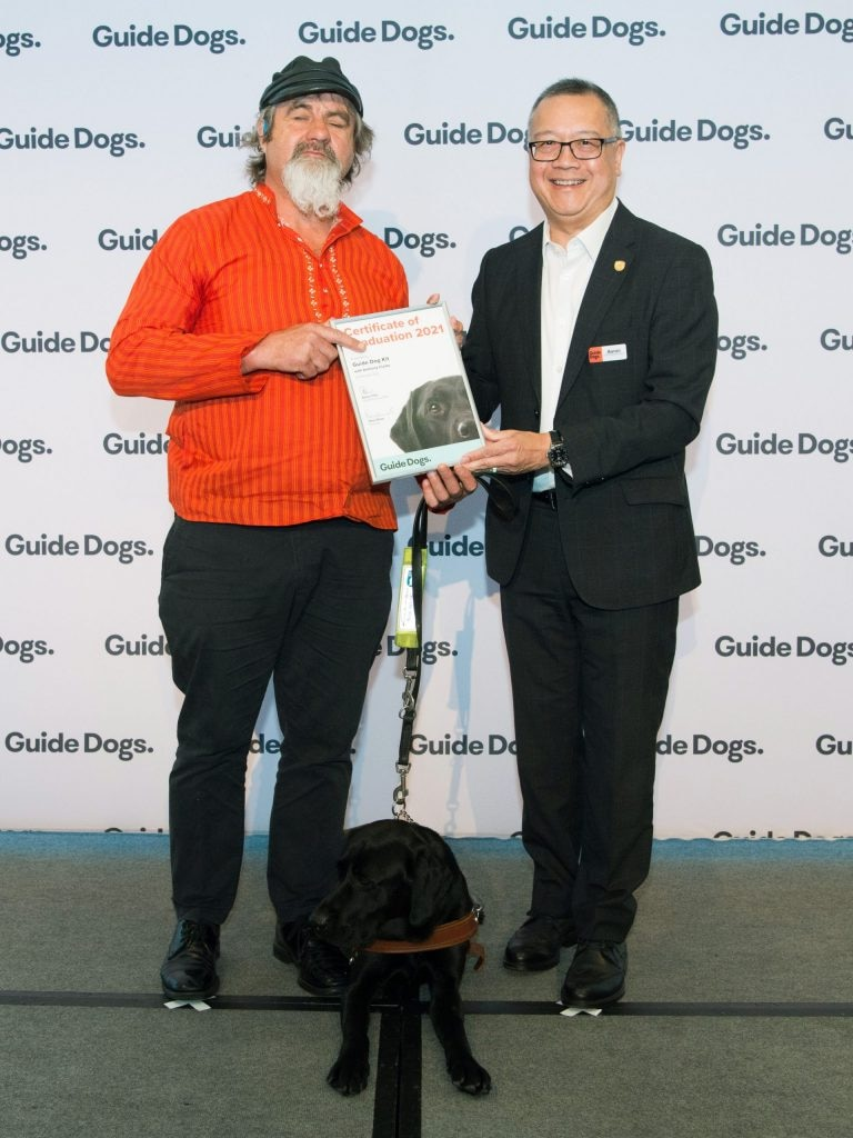 Two men holding a certificate while a black puppy sits at their feet