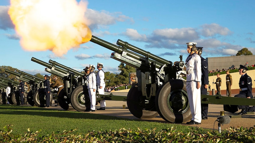 soldiers stand next to howitzers being fired on the forecourt of parliament house in the day time