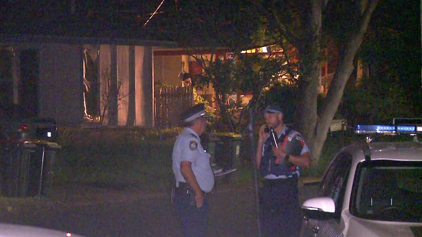 police officers standing in front of a suburban house