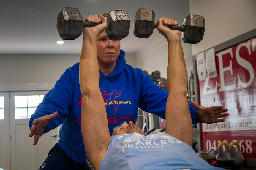 Bev lifts weights and Lee spots her.