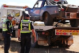 NT Police crash investigators stand next to a tow truck, with the Finke Desert Race vehicle loaded onboard.