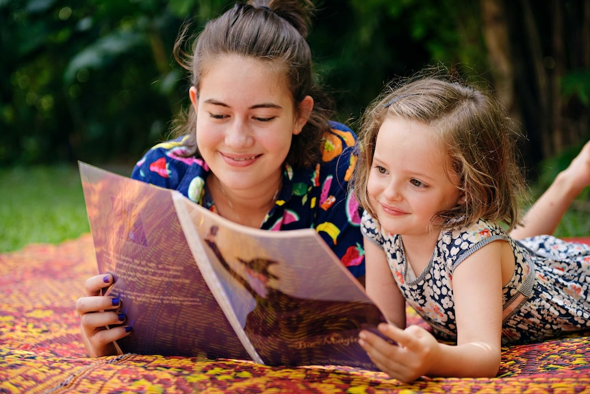 Bridget Myerscough and Vita Ralph, 6, read 'The Magic Cure' together outdoors. They're both smiling.