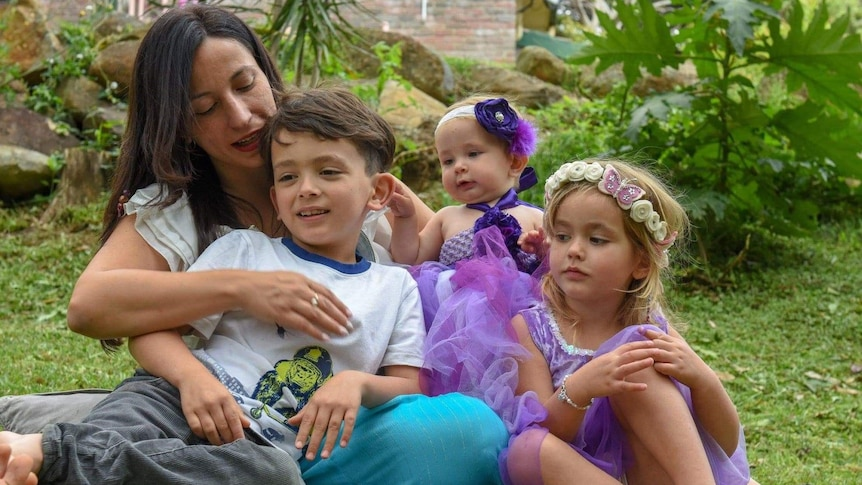A dark-haired young mother hugs her son as the pair sit with a baby and a girl of a bout four in a garden.