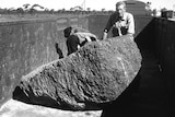 A black and white photo of three men behind a large meteorite sitting in a rail carriage.