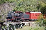 historic steam train crossing a bridge in rural area