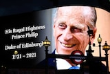 Prince Philip smiles in a picture on the screen at Piccadilly Circus in London with text with his name and birth and death date.