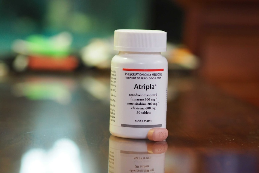 A small pill sits next to a container on a bench. The label says 'Atripla', which is an antiviral medication that treatsHIV.
