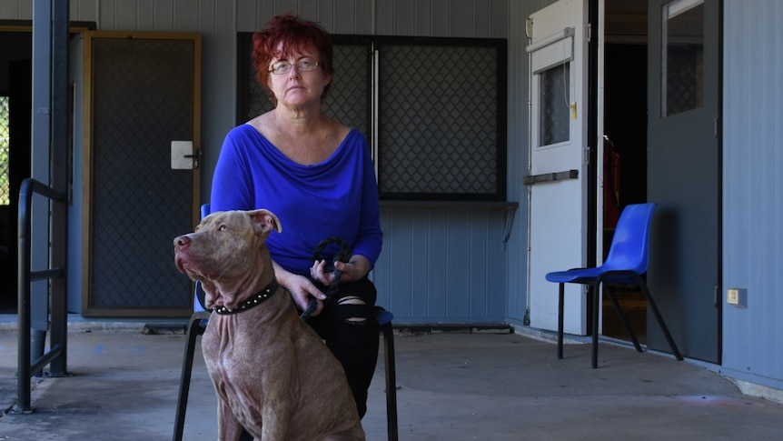 A woman in a bright blue top sits on a chair. At her feet is her grey pet dog.