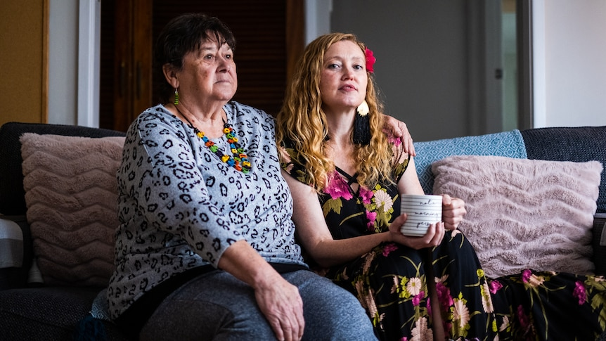 Former Jehovah's Witness Amy Whitby and her mother Theresa Claire sitting on their couch.