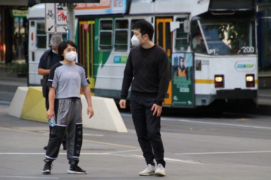 A man and child in a Melbourne street with a tram behind them.