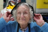 A close up shot of a smiling elderly woman putting a hat on her head