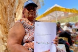 An aboriginal woman holding a paper copy of the Aboriginal Cultural Heritage Bill