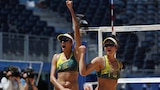 Two women wearing green and yellow bikinis raise their arms in the air