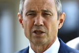 A tight head and shoulders shot of WA Health Minister Roger Cook wearing a suit and tie and talking during a media conference.