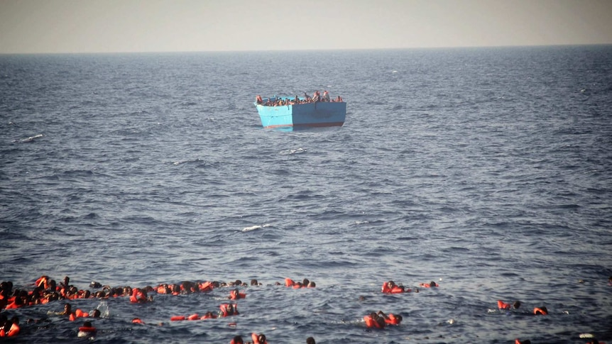 Asylum seekers wearing life vests are seen floating in the water before being rescued at sea.