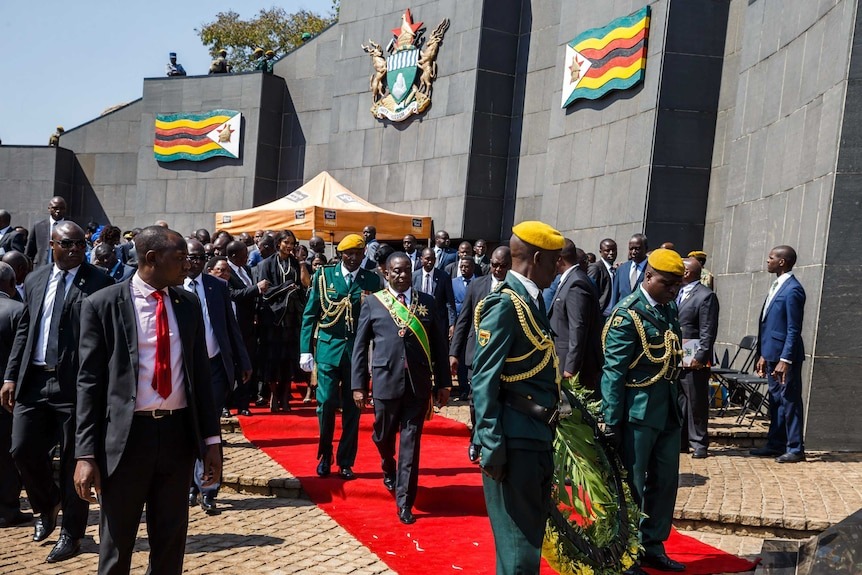 Zimbabwe President Emmerson Mnangagwa walks towards a soldier holding a wreath.