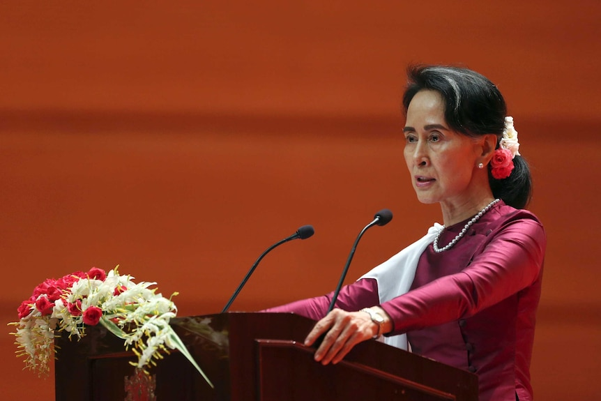 Myanmar'sState Counsellor Aung San Suu Kyi during the speech. She is standing at a podium with flowers on it.