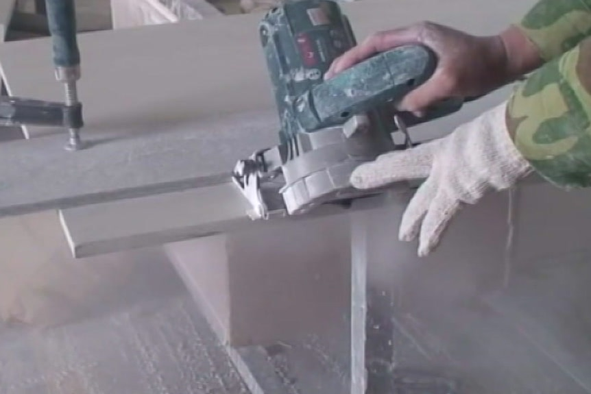 A worker cuts a slab of stone