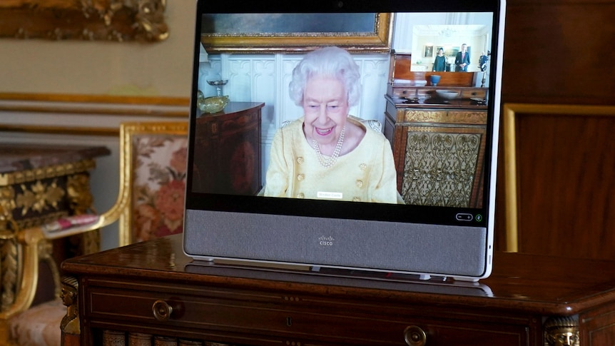 Photo shows the Queen on a tablet smiling on camera