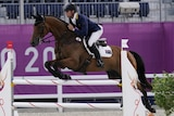 A horse and rider jump a barrier.