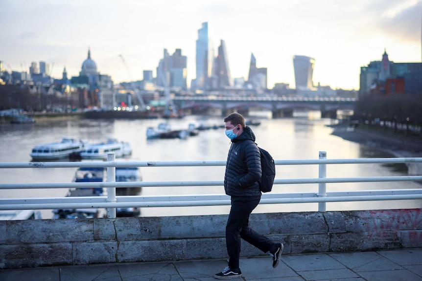 A man in a puffy jacket and face mask walks over a bridge with the London skyline behind him