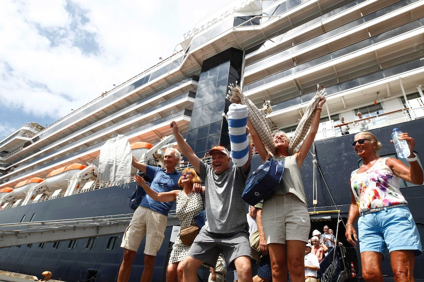 Passengers cheer as they disembark a ship