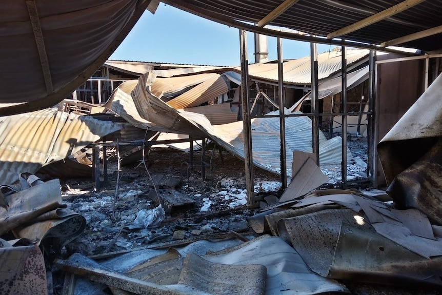 A fire-damaged building with its corrugated iron roof sheeting collapsed.