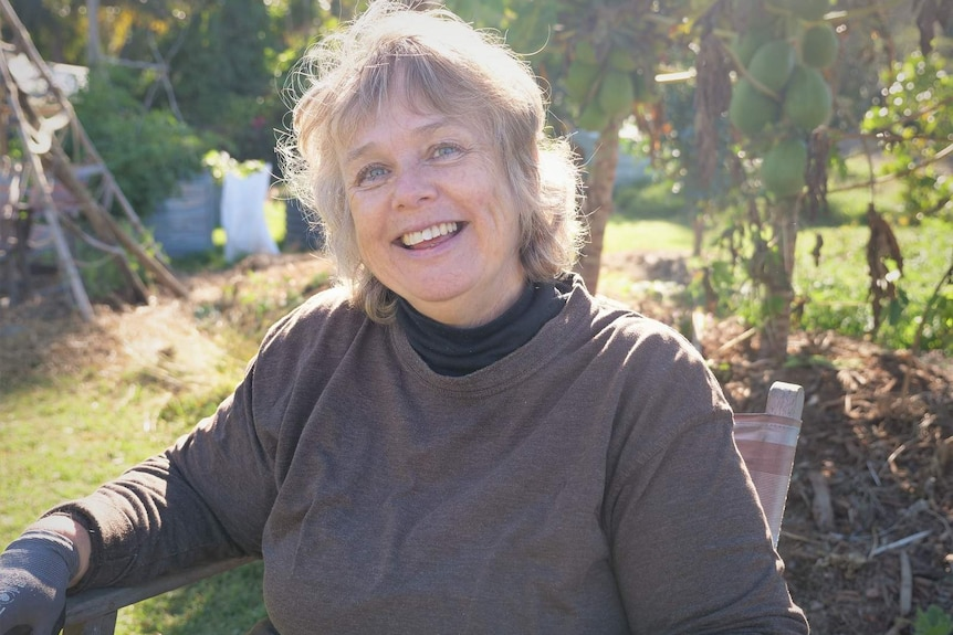 Woman, Berni Jackstas, blue eyes and short light hair sits in the garden smiling with the sun beaming down.
