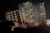 An already partially collapsed building is demolished at night.