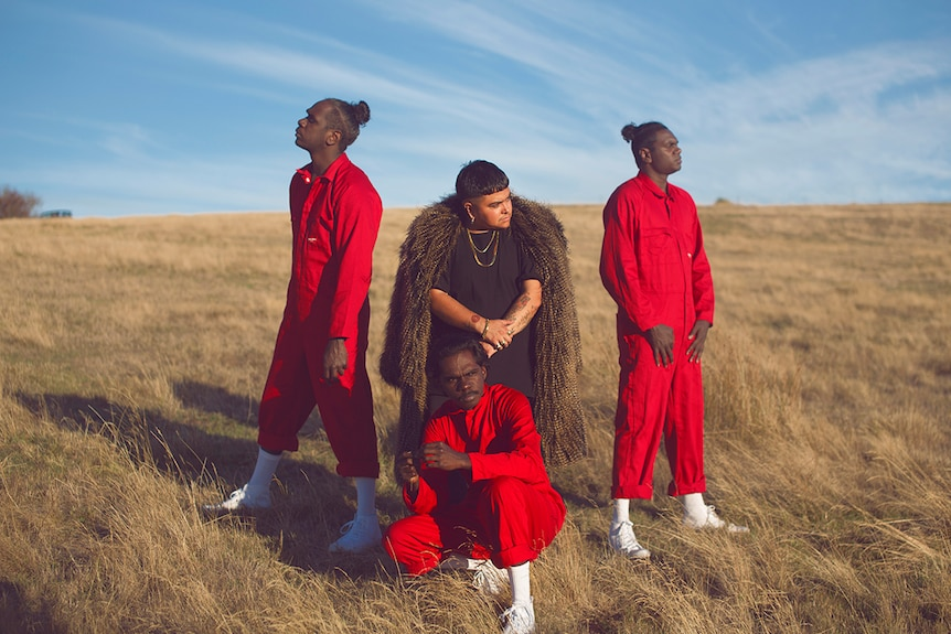 Photo of artist Mojo Juju in a feather coat and three members of Djuki Mala dance group in red jumpsuits posing on grassy plain.