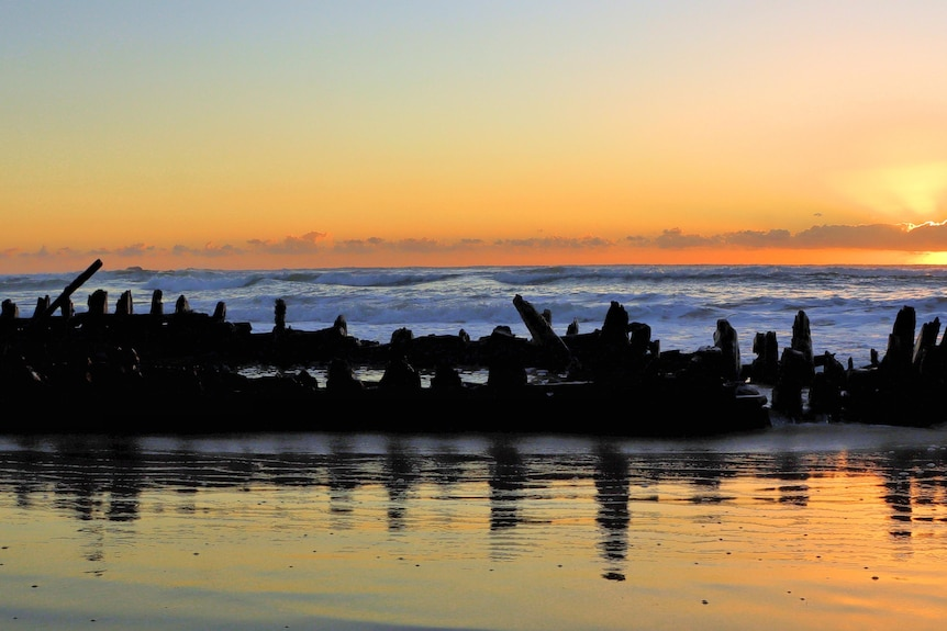 A shipwreck on a beach at sunrise.