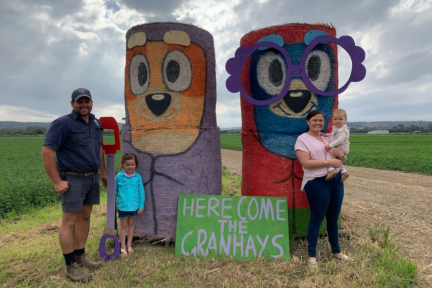 Family of four stand in front of haybales designed as characters from Bluey